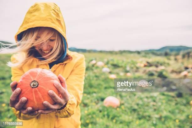 glückliche junge frau hält einen orangenkürbis in den händen - riesenkürbis stock-fotos und bilder