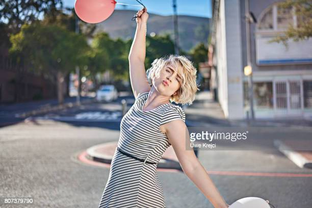 Happy young woman holding balloons
