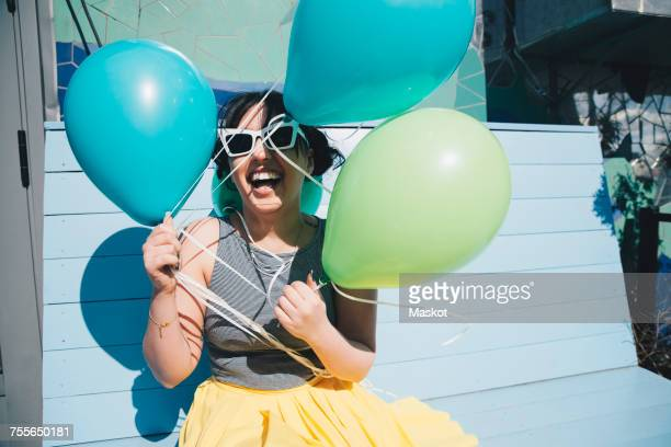 Happy young woman holding balloons while sitting on bench