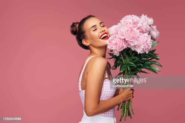 jeune femme heureuse retenant le bouquet des fleurs roses - bouquet de fleurs photos et images de collection