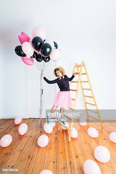 Happy young woman holding bunch of balloons indoors