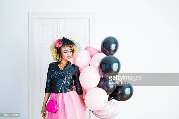Happy young woman holding bunch of balloons