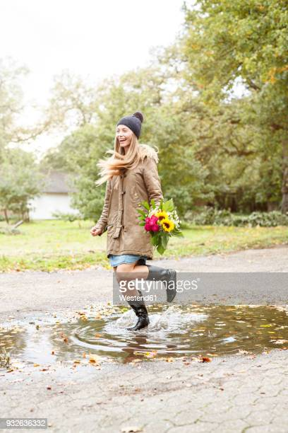 happy young woman holding bunch of flowers jumping in puddle - gummistiefel frau stock-fotos und bilder