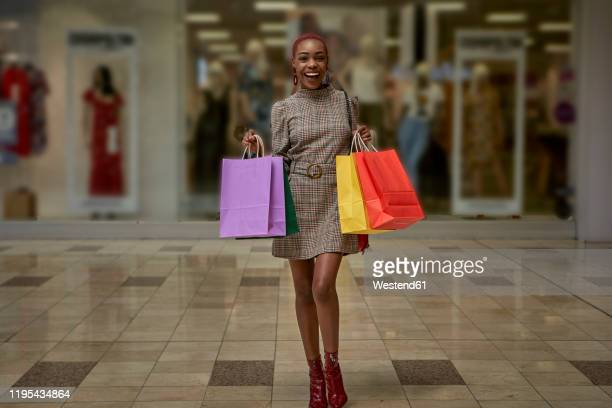 happy young woman holding colorful shopping bags walking outside a shop - multi colored dress stock pictures, royalty-free photos & images
