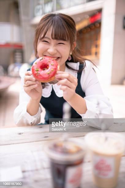 オープン カフェでドーナツを持って幸せな若い女 - 女子大生 ストックフォトと画像