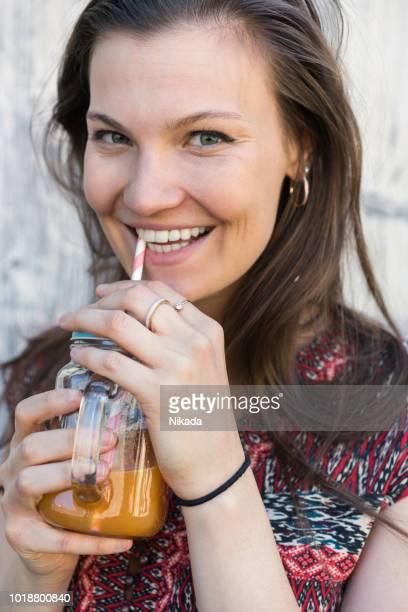 Glückliche junge Frau hält trinken vor der weißen Wand