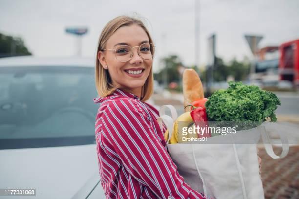 jeune femme heureux retenant des épiceries dans le sac réutilisable - buying photos et images de collection