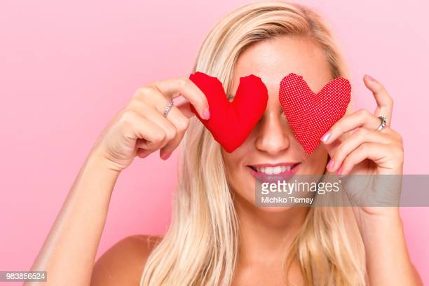 happy young woman holding heart cushions - love is blind stock pictures, royalty-free photos & images