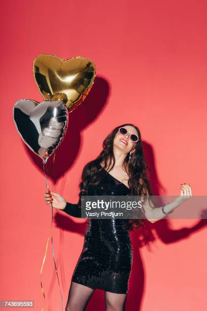 Happy young woman holding helium balloons against coral background