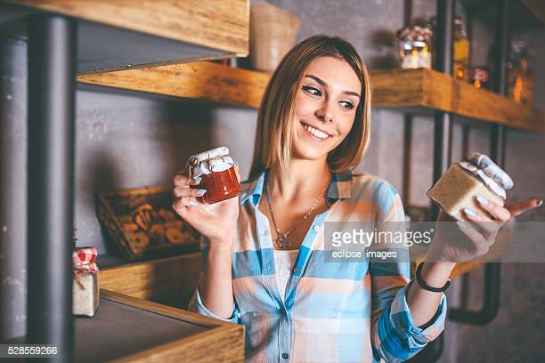 happy young woman holding jars with canned food