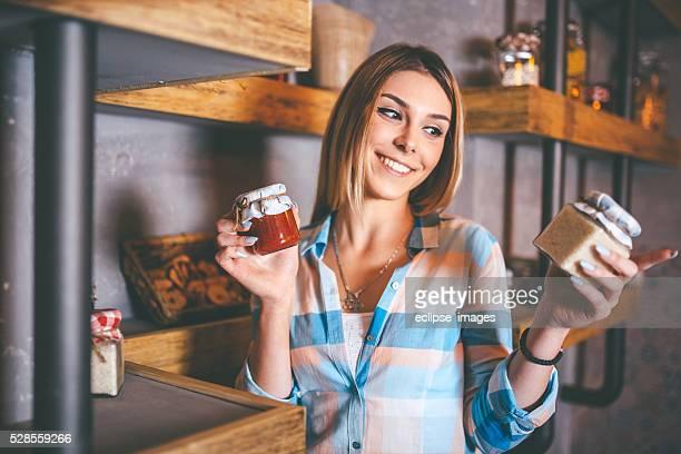 Feliz mujer sosteniendo las jarras con producto enlatado