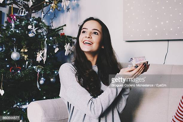 happy young woman holding paper currency by christmas tree at home - christmas cash stock pictures, royalty-free photos & images