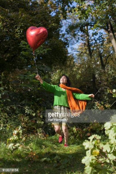 Happy young woman holding red heart shape balloon while running against trees at park