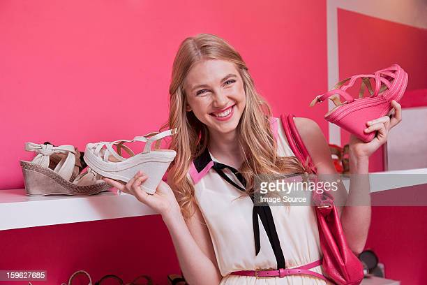 Happy young woman holding shoes in store