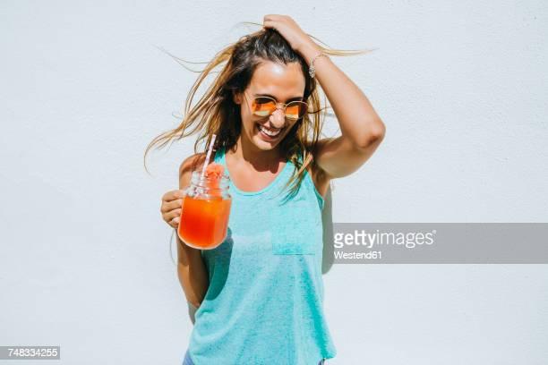 happy young woman holding watermelon drink in front of white wall - rafraîchissement photos et images de collection