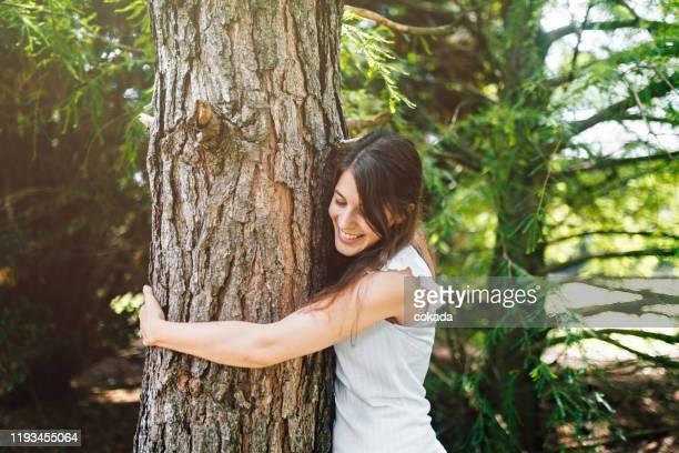 jeune femme heureux étreignant un arbre - escapade urbaine photos et images de collection
