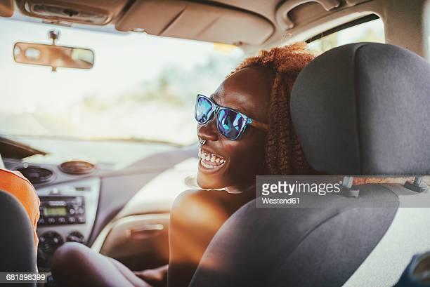 happy young woman in a car - landvoertuig stockfoto's en -beelden