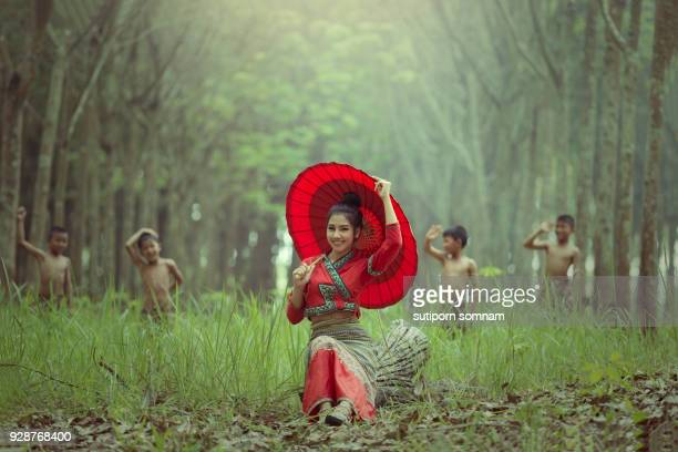Happy young woman in a red dress with a red umbrella on forest background and children