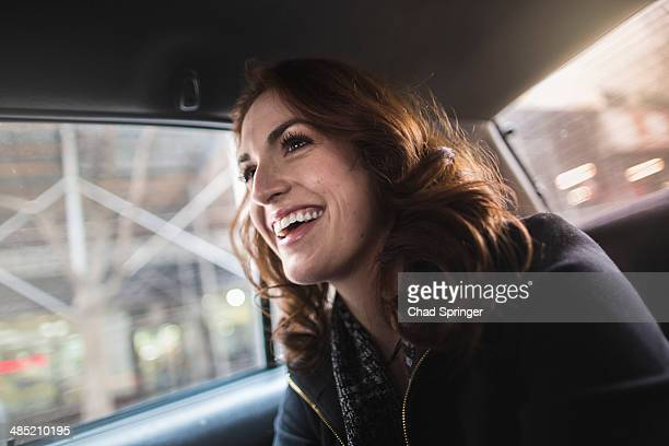 Happy young woman in back seat of taxi