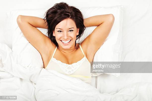 幸せな若い女性のベッド