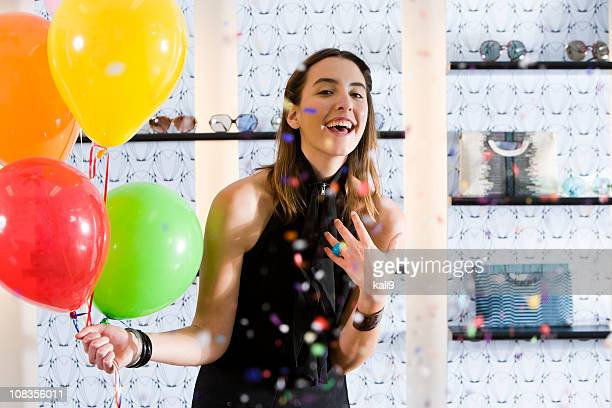 happy young woman in boutique with balloons and confetti - multi coloured purse stock photos and pictures
