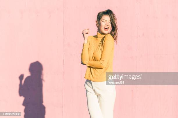 happy young woman in front of a pink wall - trousers stock pictures, royalty-free photos & images