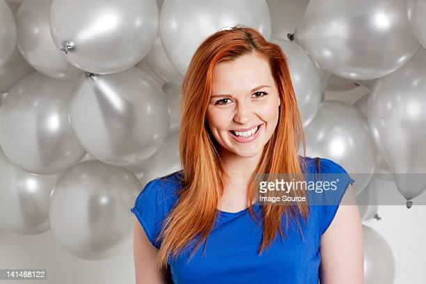 Happy young woman in front of balloons