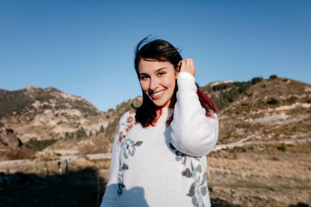 Happy young woman in front of mountain