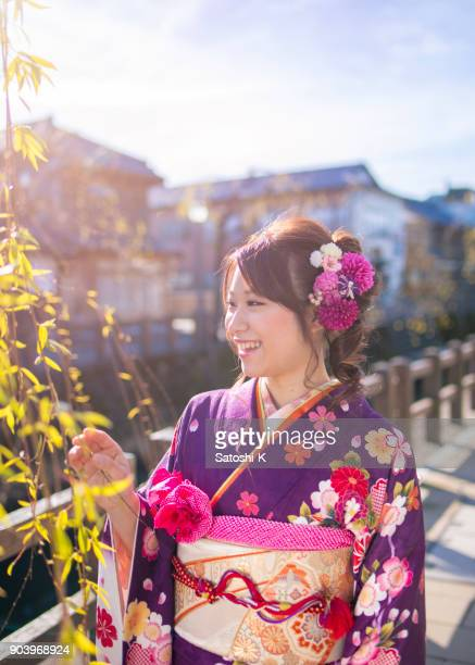 Happy young woman in furisode kimono on coming of age day