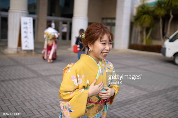 happy young woman in furisode kimono walking at coming-of-age ceremony - seijin no hi stock pictures, royalty-free photos & images