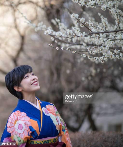 袴の卒業式の後に梅の花を見て幸せな若い女