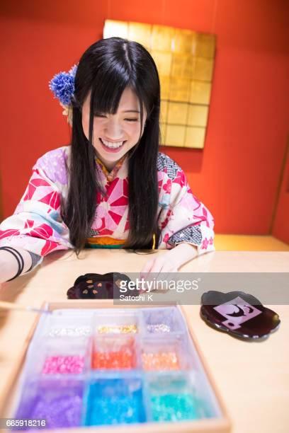 Gelukkig jonge vrouw in Kimono kleuren toe te voegen op zelf ontworpen schotel op bladgoud werkplaats plakken