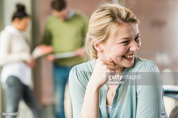 happy young woman in office with colleagues in background - premier plan net photos et images de collection