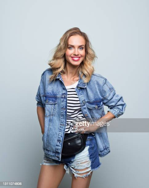 happy young woman in oversized jeans jacket - 20th century stock pictures, royalty-free photos & images