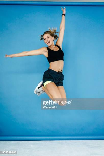 happy young woman in sportswear jumping midair - roupa desportiva imagens e fotografias de stock