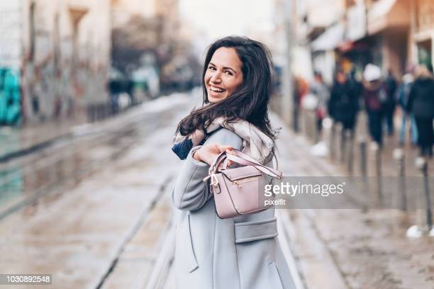 happy young woman in the city - clutch bag stock photos and pictures