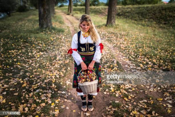 jeune femme heureux dans les fleurs traditionnelles de fixation de vêtements - serbie photos et images de collection