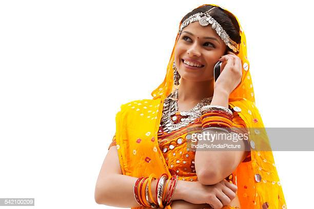 Happy young woman in traditional wear using mobile phone against white background