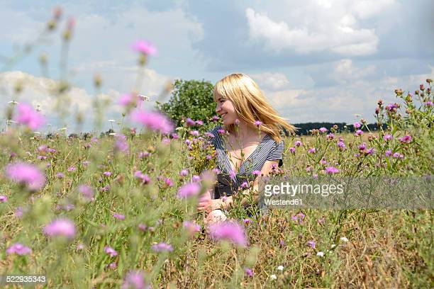 Happy young woman in wildflower meadow