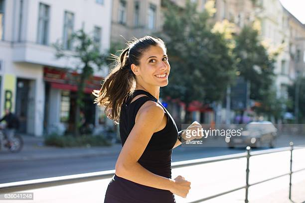 Happy young woman jogging in city