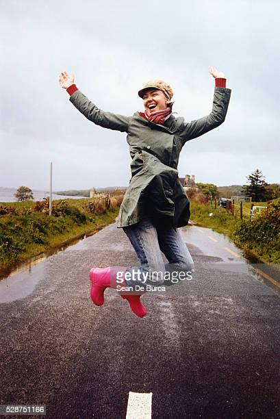 happy young woman jumping in midair - pink coat stock pictures, royalty-free photos & images