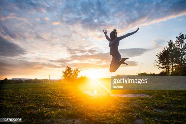 happy young woman jumping in park. - cultivated land stock pictures, royalty-free photos & images