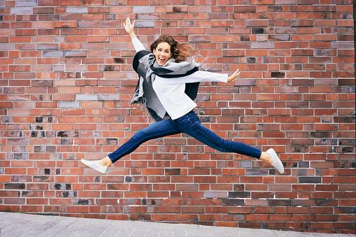 Happy young woman jumping in the air in front of brick wall - gettyimageskorea