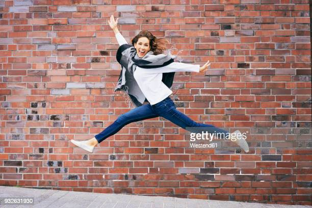 happy young woman jumping in the air in front of brick wall - leichter stock-fotos und bilder
