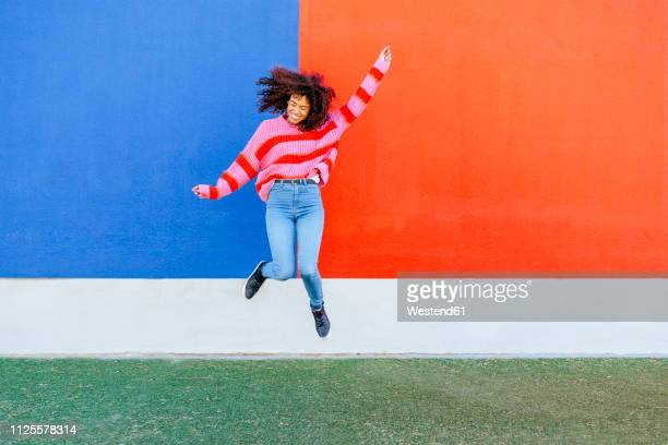 happy young woman jumping in the air - eccitazione foto e immagini stock