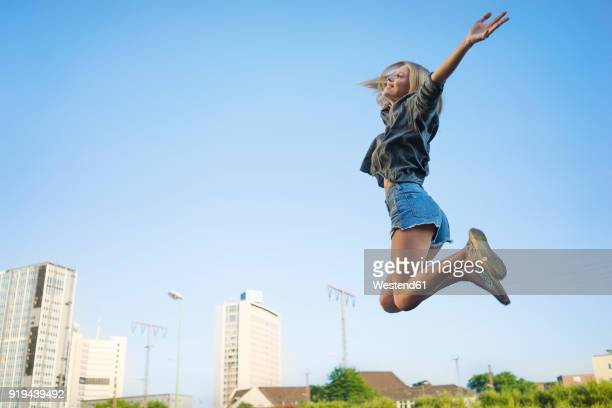 happy young woman jumping in the air - hot pants stock-fotos und bilder