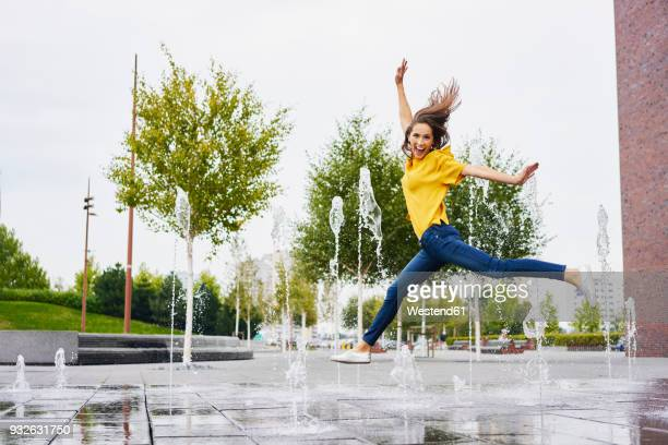 happy young woman jumping in the air - femme fontaine photos et images de collection