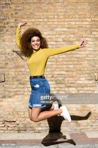 happy young woman jumping in the air - black skirt stock pictures, royalty-free photos & images