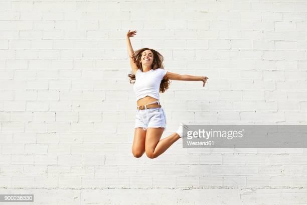 happy young woman jumping mid-air in front of white wall - bonito pessoa imagens e fotografias de stock