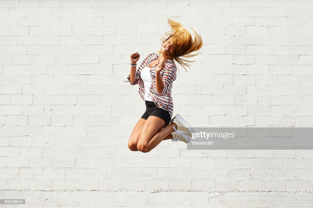 Happy young woman jumping mid-air in front of white wall : Stock-Foto
